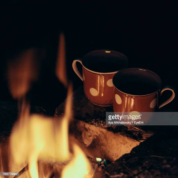 Close-Up Of Tea Cup By Campfire At Night