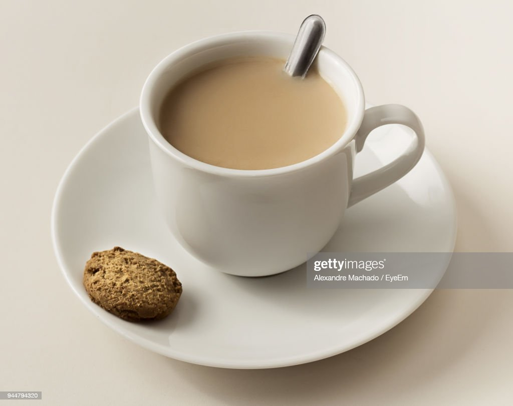 Close-Up Of Tea Cup With Cookie On Table : Stock Photo