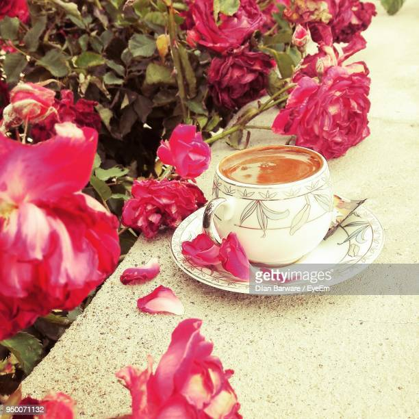 Close-Up Of Tea In Cup By Flowers Blooming Outdoors