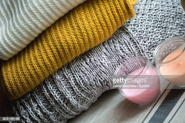 Close-Up Of Tea Light Candles By Stacked Sweaters On Table