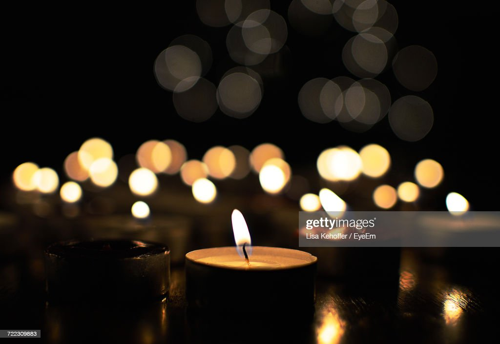Close-Up Of Tea Light Candles In Darkroom : Stock Photo