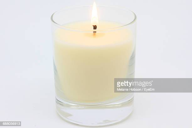 close-up of tea light over white background - candle stock pictures, royalty-free photos & images