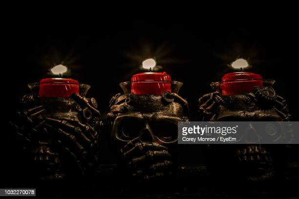 close-up of tea lights on skeleton head over black background - flame monroe stock photos and pictures