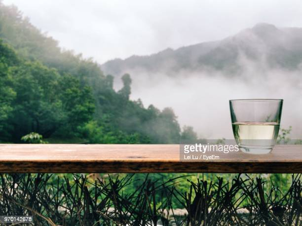 Close-Up Of Tea On Wooden Table Against Trees During Foggy Weather