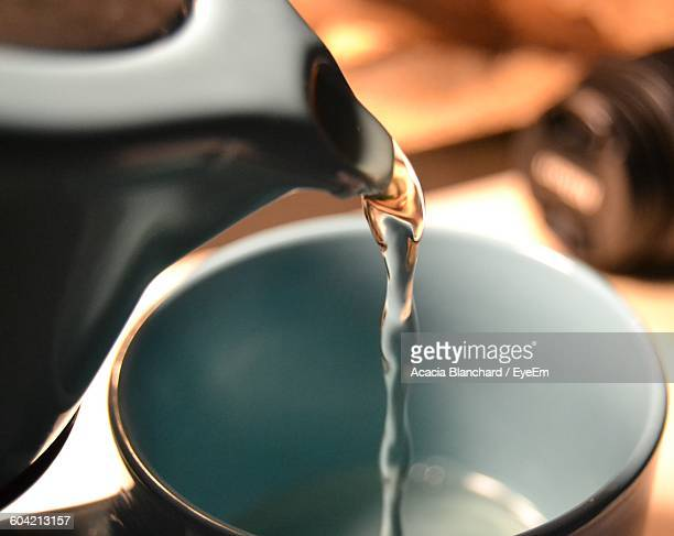 Close-Up Of Teapot Pouring Water In Cup
