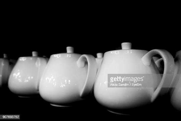 Close-Up Of Teapots Against Black Background