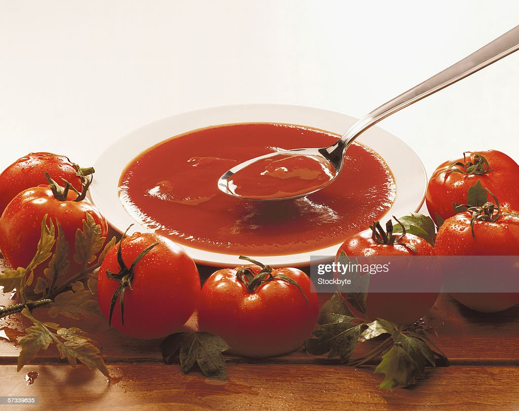 close-up of teaspoon in a bowl of tomato sauce surrounded by whole tomatoes : Stock Photo