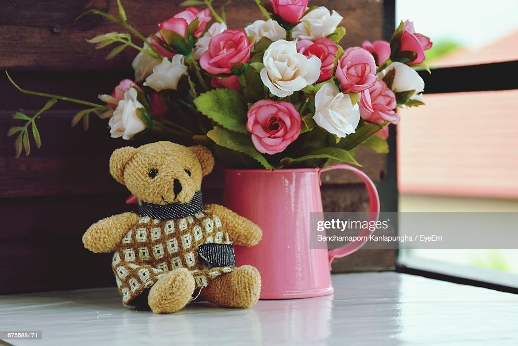 Closeup Of Teddy Bear With Roses In Vase By Window Stock Photo