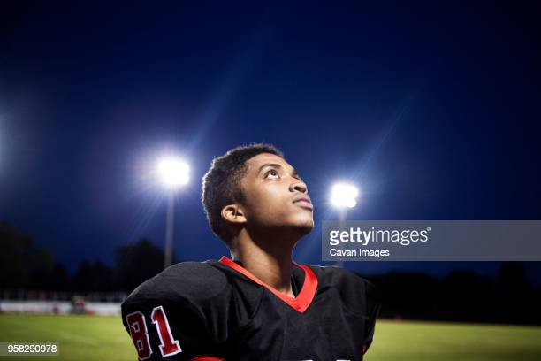 close-up of teenage american football player looking up at illuminated field - high school football stock pictures, royalty-free photos & images