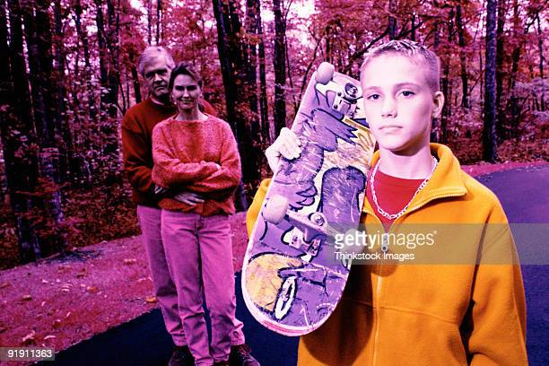 Close-up of teenage boy holding up skateboard