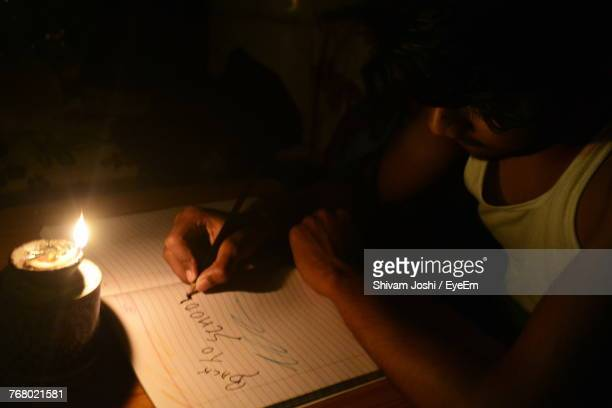 Close-Up Of Teenage Boy Writing In Book
