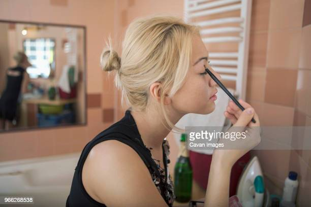 close-up of teenage girl applying eyeshadow in bathroom - girl in mirror stock photos and pictures