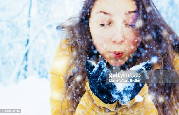 close-up of teenage girl blowing snow on hands during winter - finland stock pictures, royalty-free photos & images