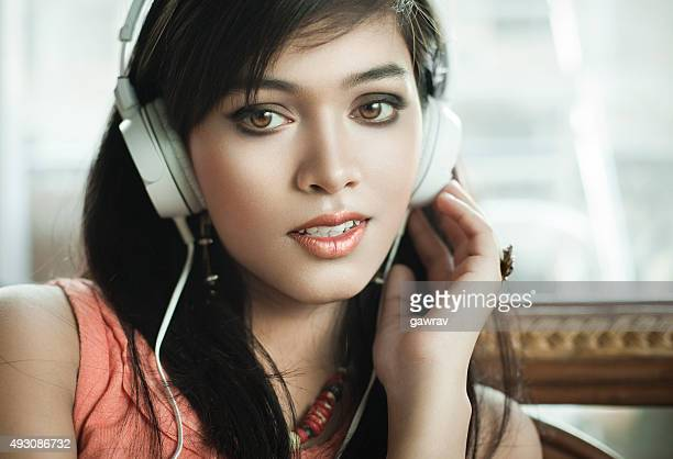 Close-up of teenage Girl listening music through headphones.