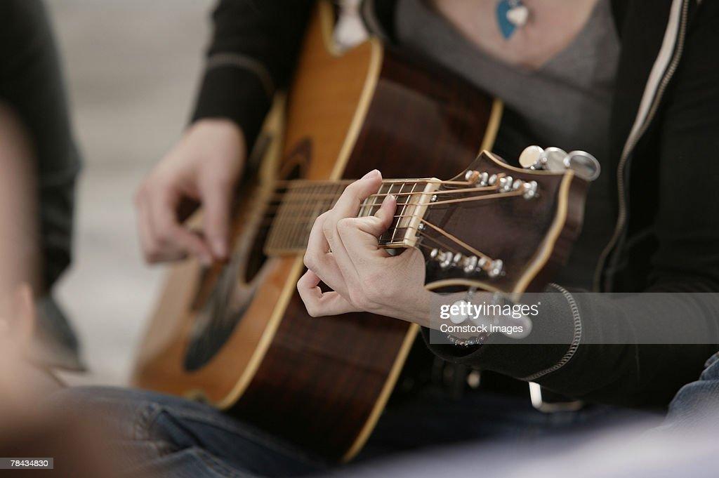Close-up of teenage girl playing guitar : Stockfoto