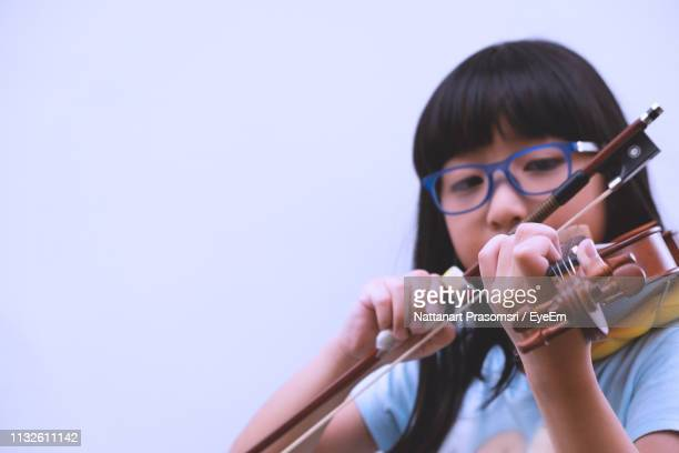 close-up of teenage girl playing violin against white background - musical instrument stock pictures, royalty-free photos & images