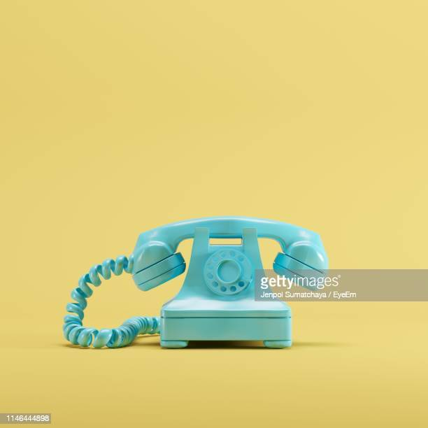 close-up of telephone against yellow background - cuadrado composición fotografías e imágenes de stock