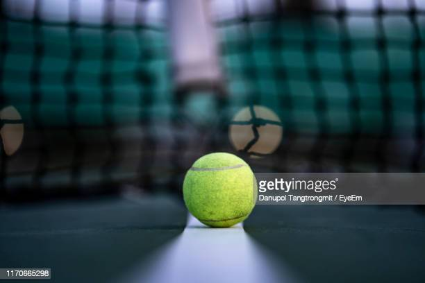 close-up of tennis ball against net at sports court - tennis stockfoto's en -beelden