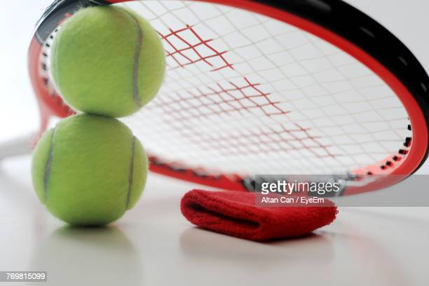 Close-Up Of Tennis Ball And Racket With Armband On White Background