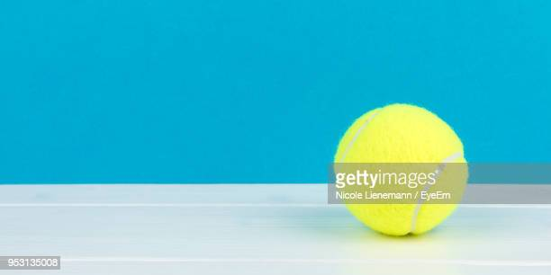 Close-Up Of Tennis Ball On Table Against Blue Background