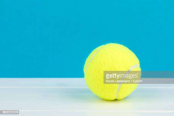 close-up of tennis ball on table against blue wall - テニスボール ストックフォトと画像