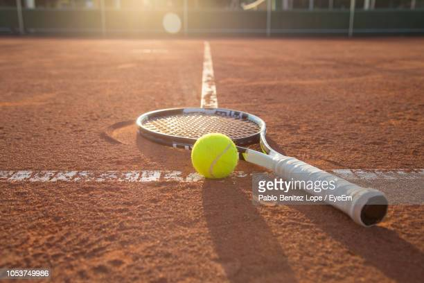 close-up of tennis racket and ball on court during sunset - ラケット ストックフォトと画像
