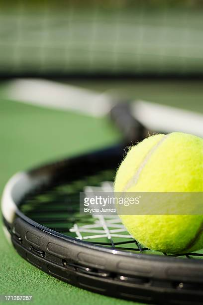 Close-up of tennis racket on court with tennis ball on top