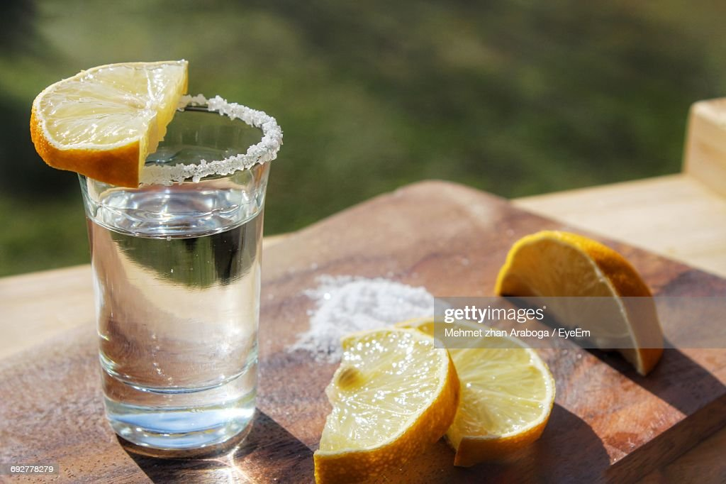 Close-Up Of Tequila Shot With Lemons Slices On Cutting Board : Stock Photo