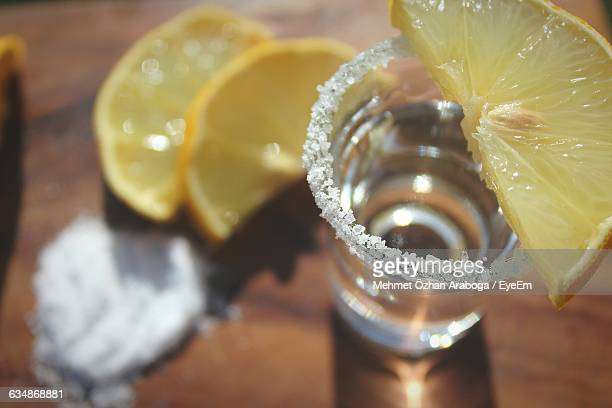 Close-Up Of Tequila With Lemons Slices And Salt Served On Table