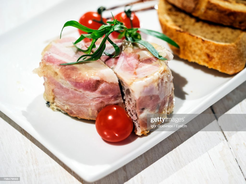 Close-Up Of Terrine With Bacon And Tomatoes In Plate On Table : Stock Photo