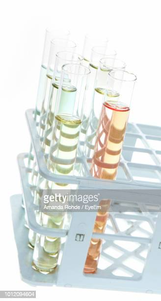 Close-Up Of Test Tubes In Rack Against White Background