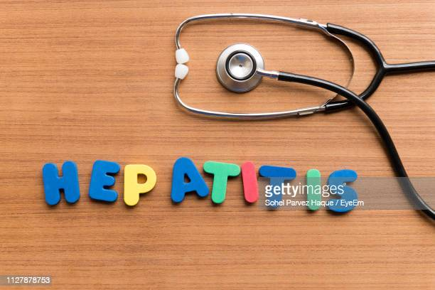 close-up of text and stethoscope on wooden table - hepatitis stock pictures, royalty-free photos & images