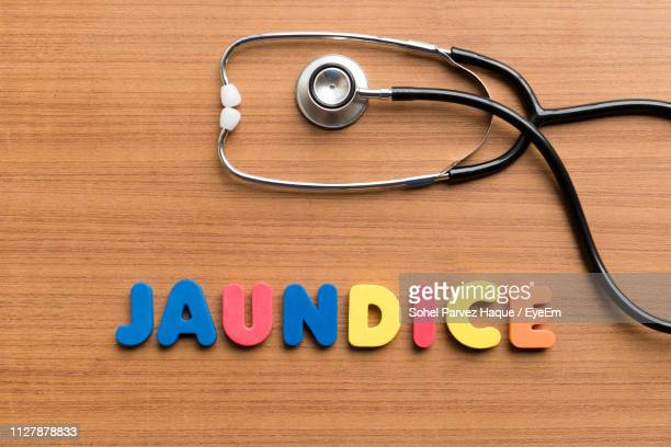Close-Up Of Text And Stethoscope On Wooden Table