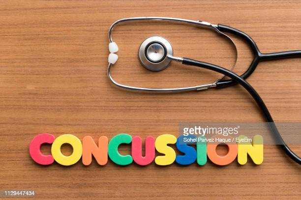 close-up of text and stethoscope on wooden table - concussion stock photos and pictures