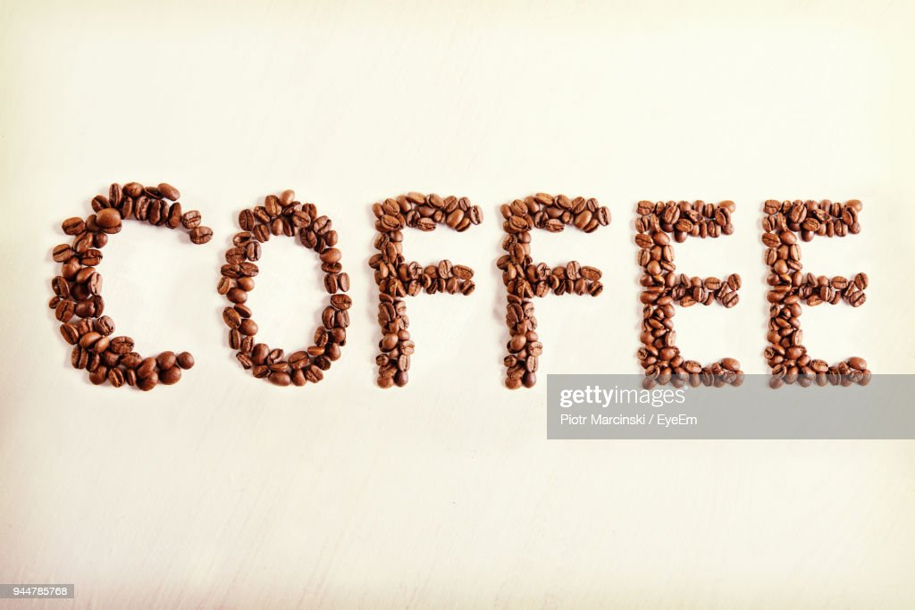 Close-Up Of Text Made With Roasted Coffee Beans Over White Background : Stock Photo