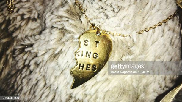 Close-Up Of Text On Heart Shape Pendant Over Rug