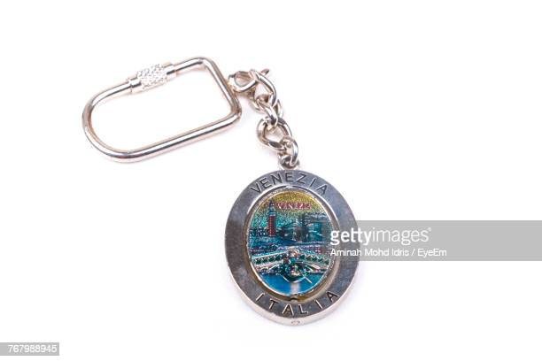 Close-Up Of Text On Keyring Charm Over White Background