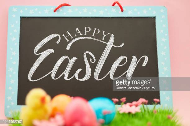 close-up of text on slate by easter eggs - happy easter text stock pictures, royalty-free photos & images