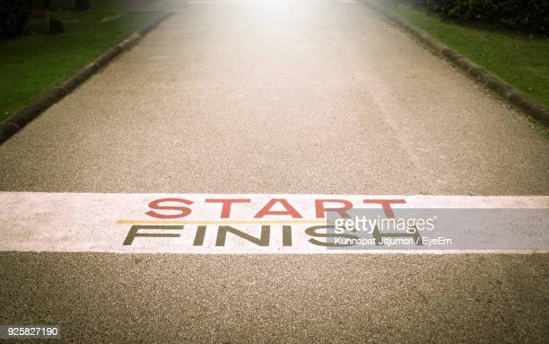 close-up of text on street by field - finish line stock pictures, royalty-free photos & images