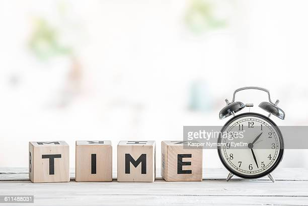 Close-Up Of Text On Wooden Blocks By Alarm Clock On Table