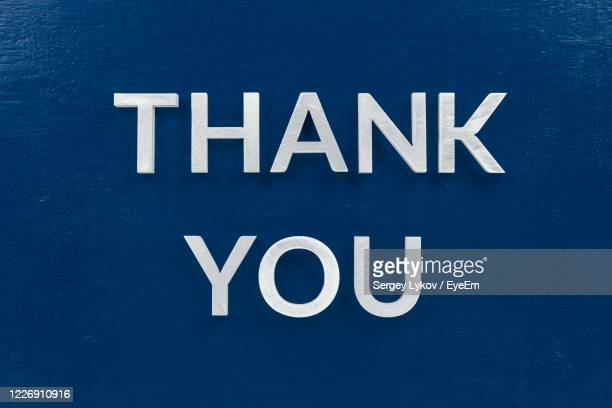 close-up of thank you text on blue table - thank you stock pictures, royalty-free photos & images