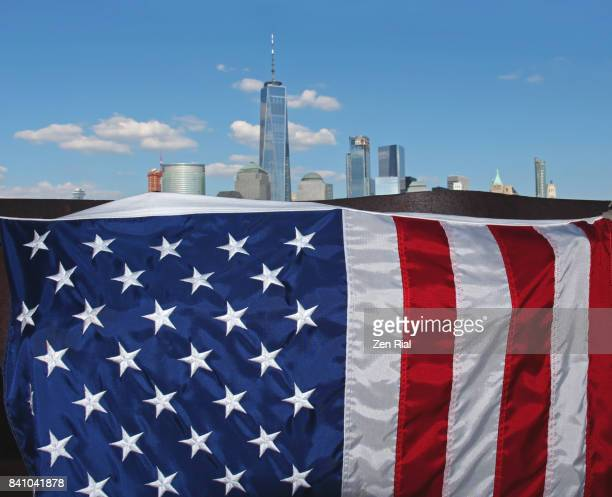 Close-up of the American flag with Lower Manhattan skyline in the background