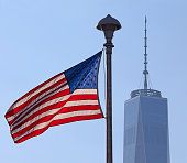 Close-up of the American flag with the Freedom Tower in the background