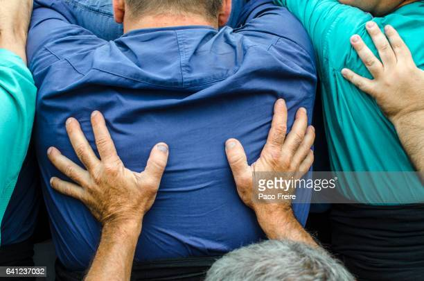 "close-up of the back and the hands of the ""castellers"" who form the core of a catalan human tower - castellers stock photos and pictures"