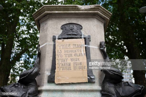 A closeup of the base of the Edward Colston statue plinth with a tapedon cardboard message saying this plaque is dedicated to the slaves that were...