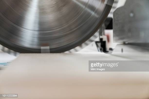 Closeup of the blade on a radial saw in a woodworking factory.