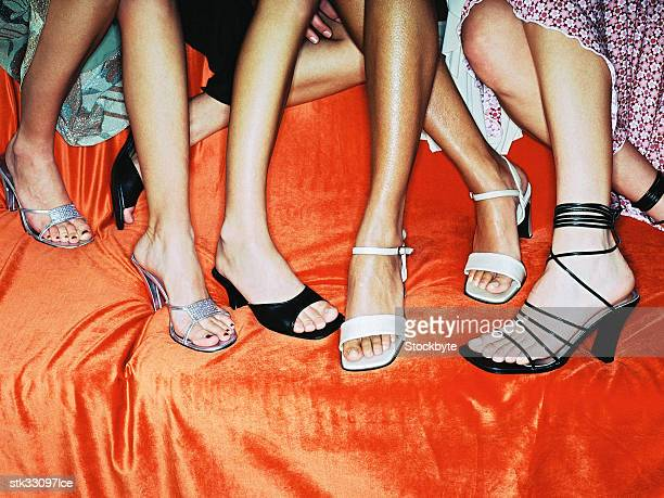 close-up of the feet of a group of women sitting at a party - black shoe stock photos and pictures