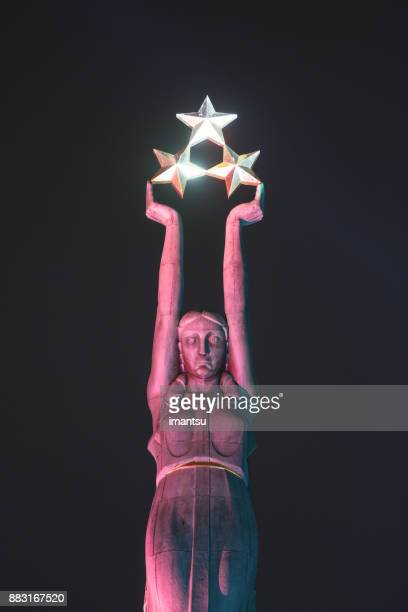 """closeup of the freedom monument of latvia in the nighttime amidst the festival """"staro riga"""" - monument stock pictures, royalty-free photos & images"""
