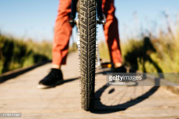 close-up of the front wheel of a bike on a wooden walkway - low section stock pictures, royalty-free photos & images