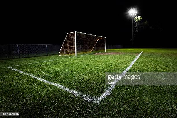 Closeup of the goalpost in a soccer field at night